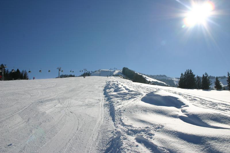 Schipiste in Kirchberg in Tirol unter blauem Himmel und Sonnenschein