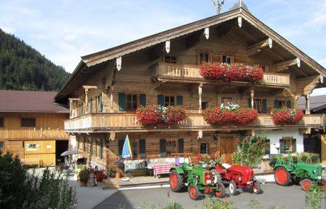 Der Peternhof im Sommer mit Oldtimer-Traktoren und Blumenschmuck