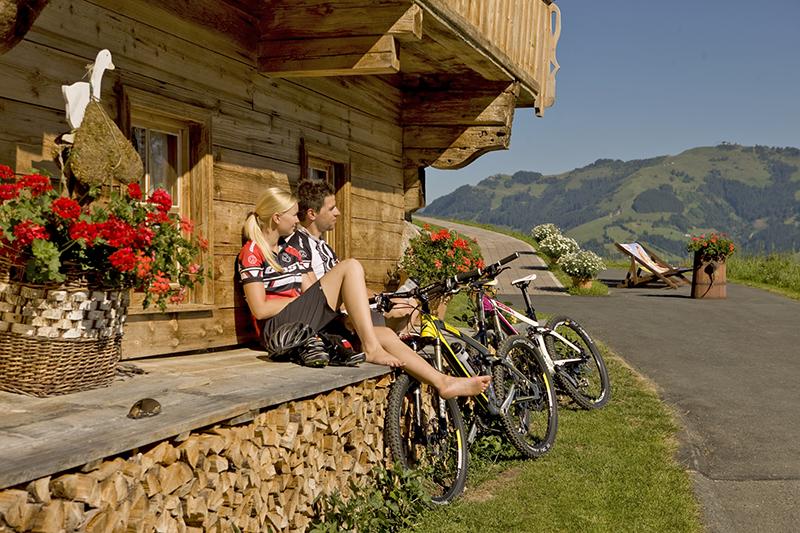 Pärchen mit Mountainbikes vor einem Bauernhof in Kirchberg in Tirol
