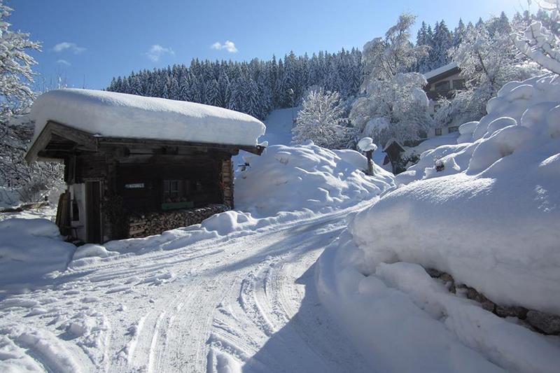 Tief verschneites Brunnenhäuschen vor dem Peternhof in Kirchberg in Tirol